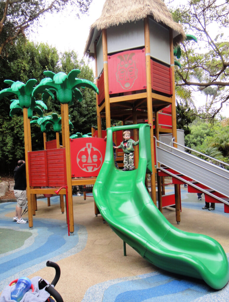 Playground with little boy standing on edge of green slide
