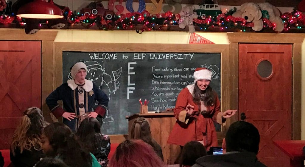 Two of Santa's elves standing in front of a chalk board