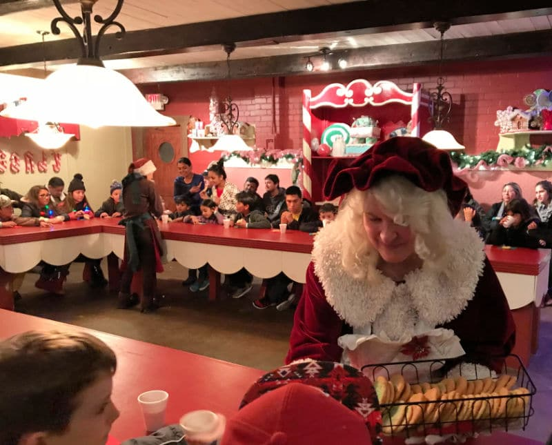 Mrs. Claus passing out cookies to children in Santa's Workshop during the North Pole Experience