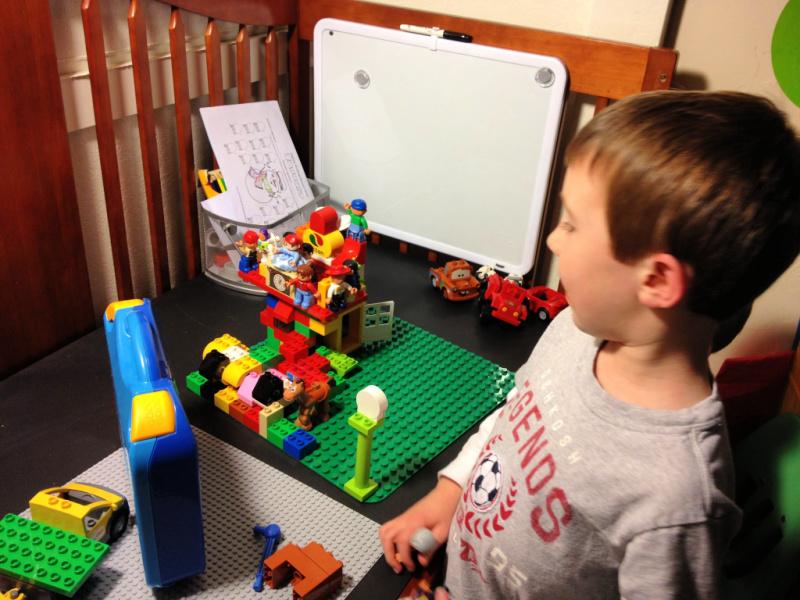 Preschooler playing on crib desk with LEGO bricks