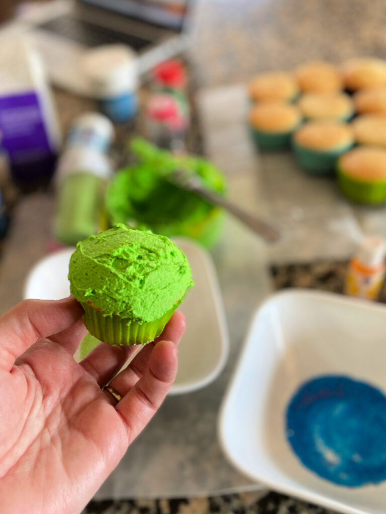 bright green cupcake held over baking supplies