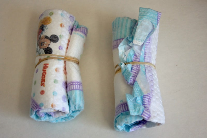 2 baby diapers rolled up and secured with rubber bands