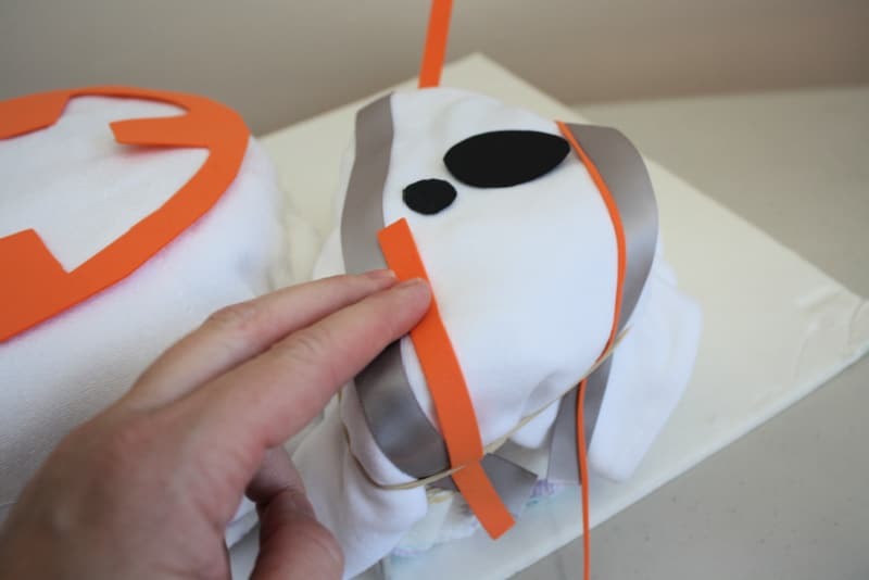 hand adding ribbon details to top of BB-8 Diaper cake