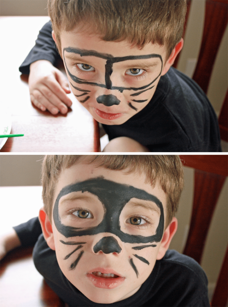little boy with a black mask, nose and whiskers painted on