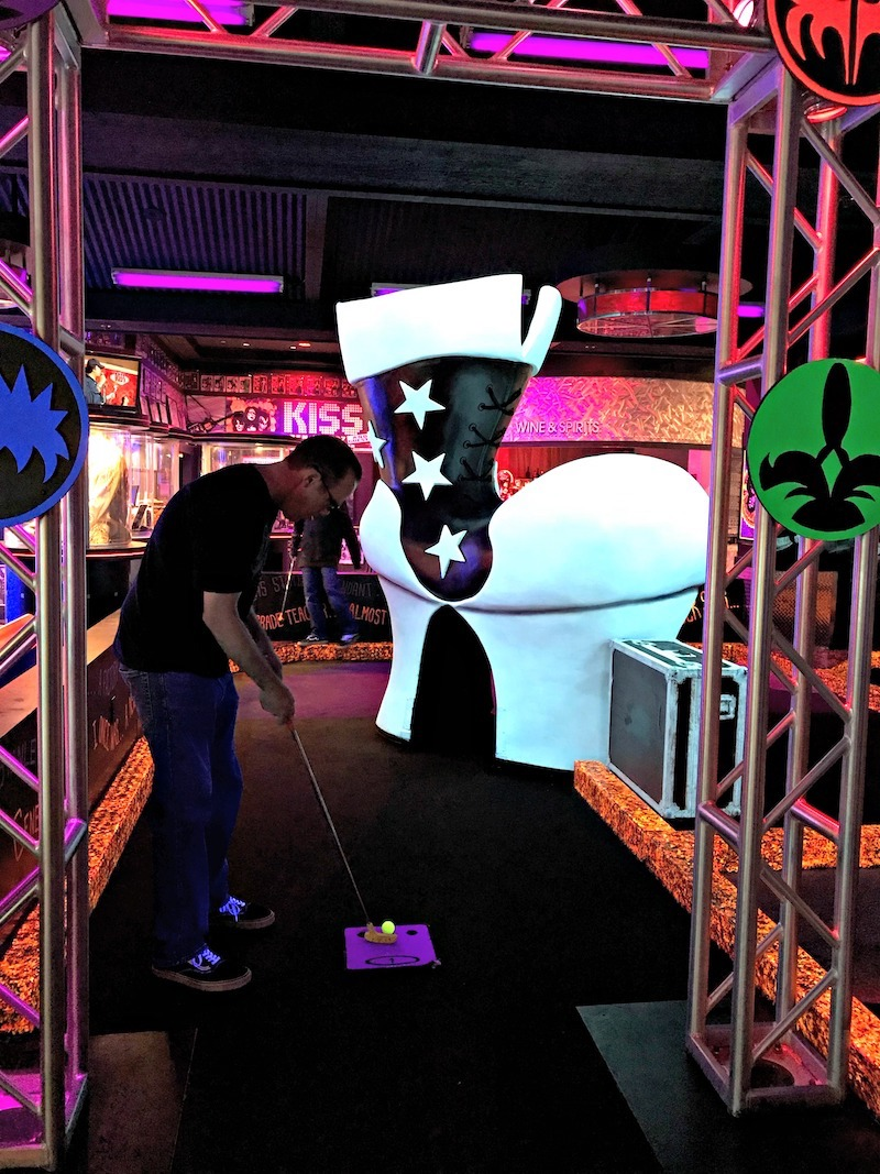 Man playing mini golf at KISS themed course