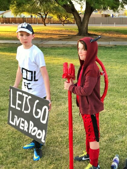 Two children dressed in super soccer fan costumes, one for Liverpool FC and the other a red devil for Manchester United