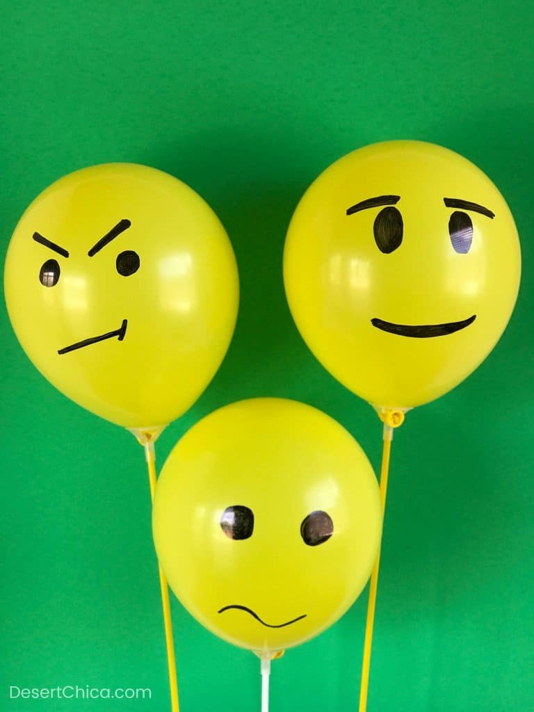 Yellow balloons with faces drawn on them to create LEGO Minifigure heads for a LEGO birthday party idea
