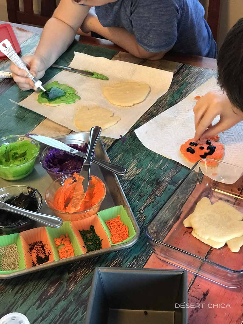 People decorating halloween cookies