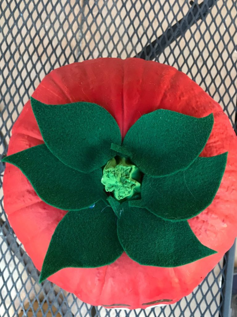 Pumpkin craft painted red with green leaves
