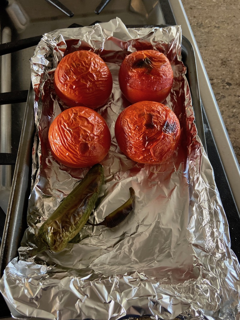 Roasted tomatoes and peppers in foil lined pan for salsa recipe
