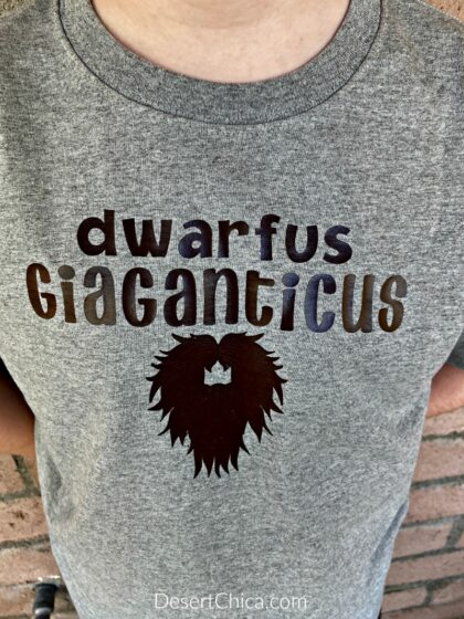 """grey t-shirt featuring a brown design of a dwarf beard that says """"dwarfus Giaganticus' inspired by Mulch Diggum from Artemis Fowl"""