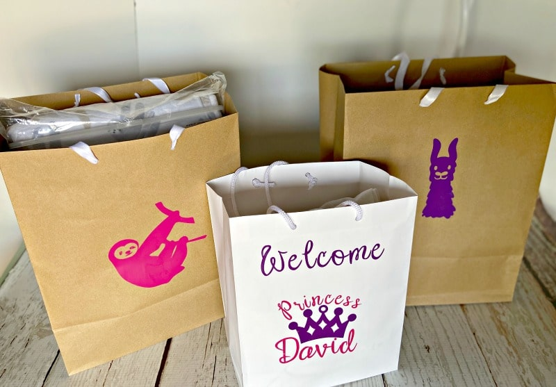 baby shower gift bags featuring a sloth, llama and princess crown made with Cricut Joy and vinyl