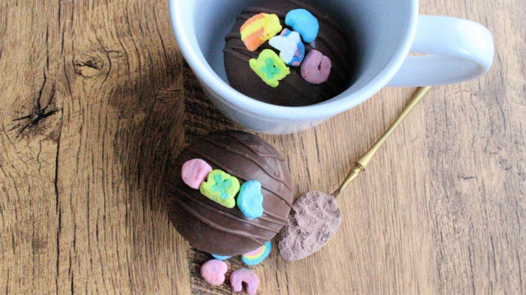 White mug with hot cocoa bomb inside with Lucky Charms Marshmallows