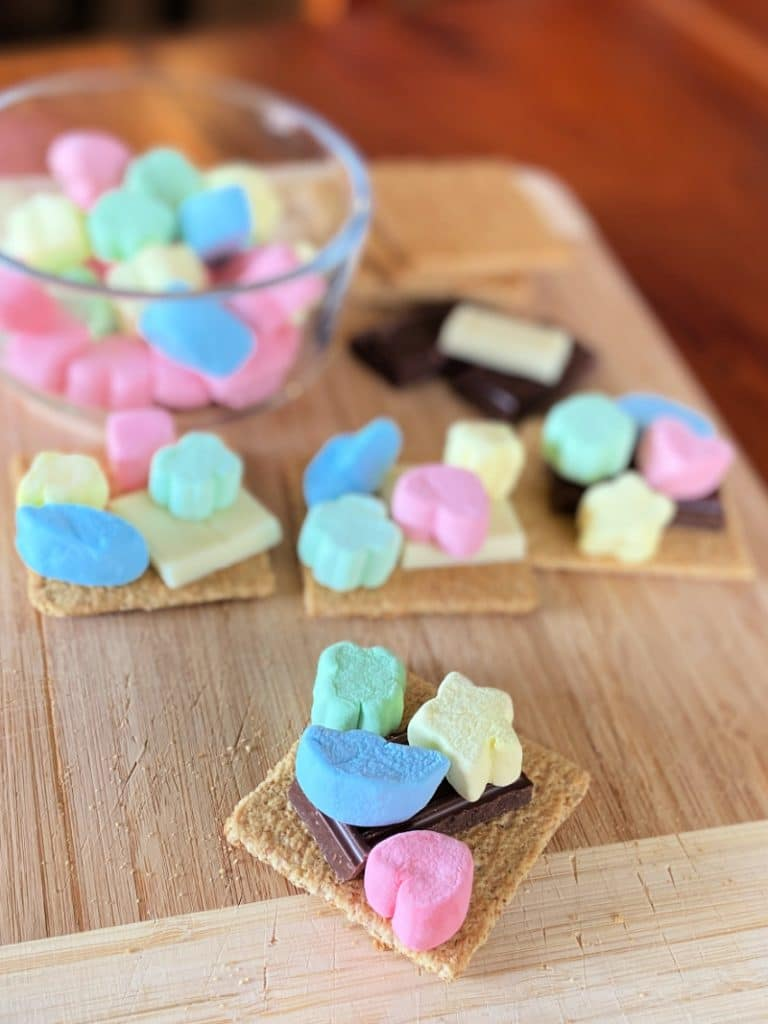 colorful lucky charms marshmallows, graham crackers and chocolate for smores