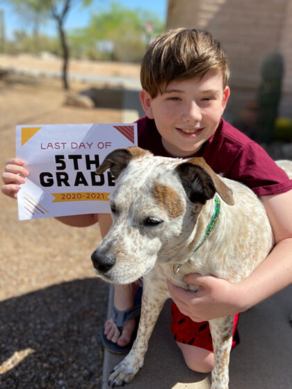 Boy and dog with a last day of 5th grade school sign