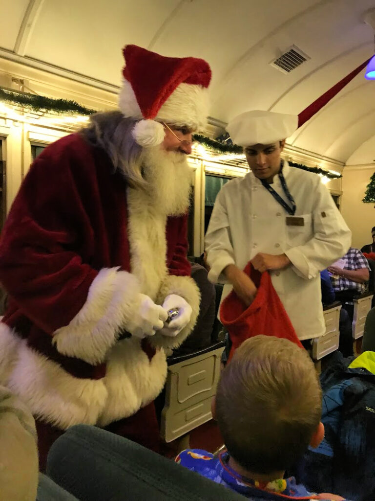 Santa talking to a boy with Polar Express waiter standing by