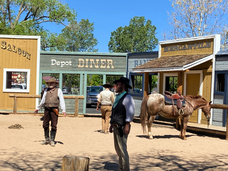 cowboys in front of a old west town facade during the show before the Grand Canyon Railway train leaves