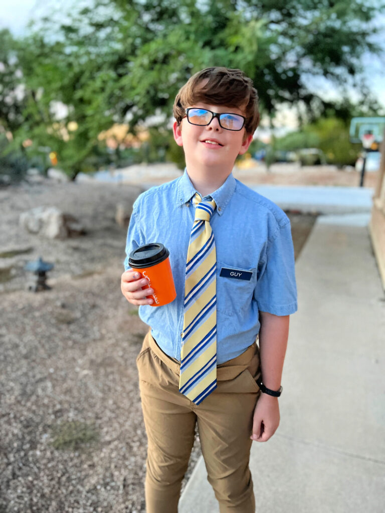 kid with glasses and yellow tie holding an orange coffee cup
