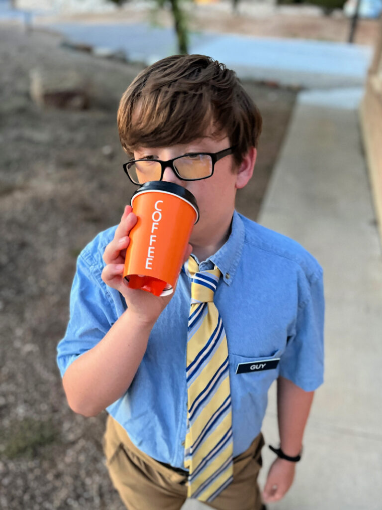 kid with black glasses drinking out of an orange coffee cup