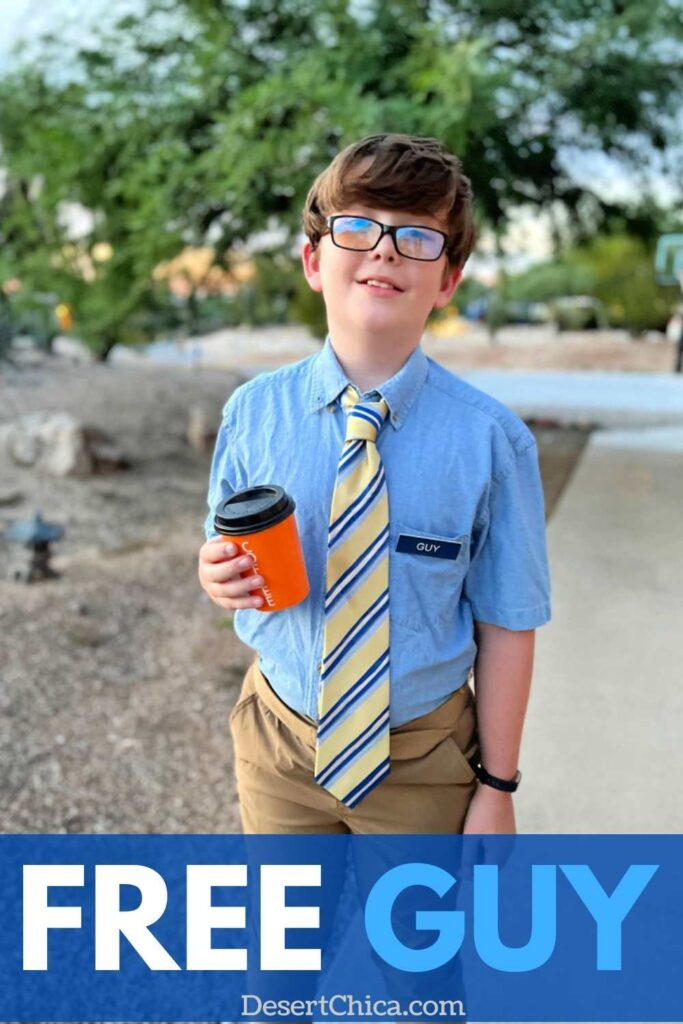 kid dresses in blue shirt, yelloe and blue tie holding an orange coffee cup
